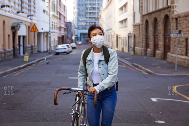 A mixed race woman with dark hair walking her bike in the city streets during the day while wearing a face mask against air pollution and corona virus