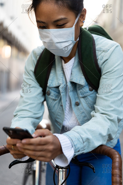Front view close up of a mixed race woman with dark hair out and about in the city streets during the day, wearing a face mask against air pollution and coronavirus, standing and leaning on her bicycle and using a smartphone with buildings in the background.