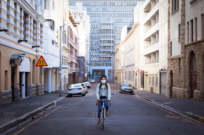 Front view of a mixed race woman with dark hair riding her bike in the city streets during the day while wearing a face mask against air pollution and corona virus