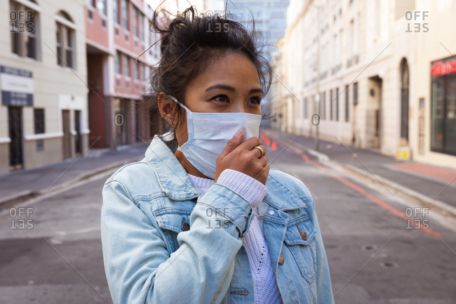 Front view of a mixed race woman with long dark hair out and about in the city streets during the day, wearing a face mask against air pollution and coronavirus, standing with a hand to her mouth with buildings in the background.