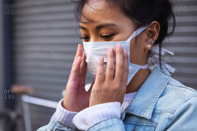 Side view close up of a mixed race woman with dark hair out and about in the city streets during the day, wearing a face mask against air pollution and coronavirus, standing with hands to her mouth with her bicycle in the background.