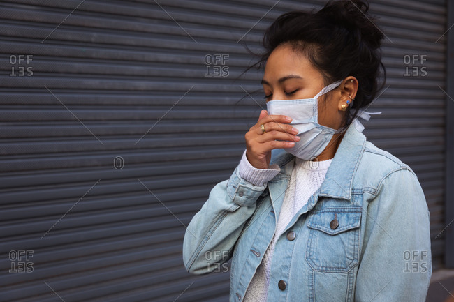 Side view of a mixed race woman with long dark hair out and about in the city streets during the day, wearing a face mask against air pollution and coronavirus, standing with a hand to her mouth with grey wall in the background.