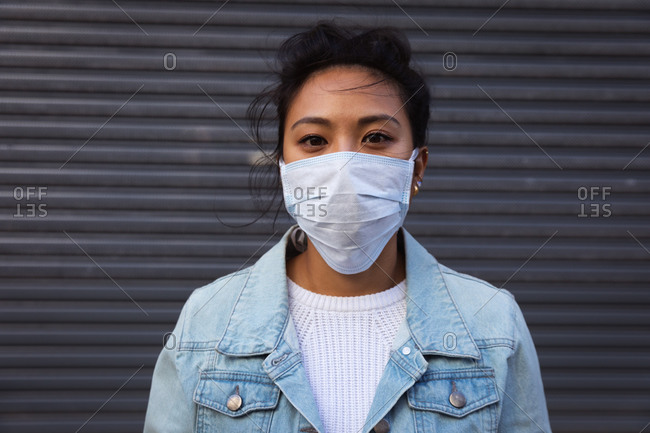 Portrait of a mixed race woman with long dark hair out and about in the city streets during the day, wearing a face mask against air pollution and coronavirus, standing and looking at camera with grey wall in the background.