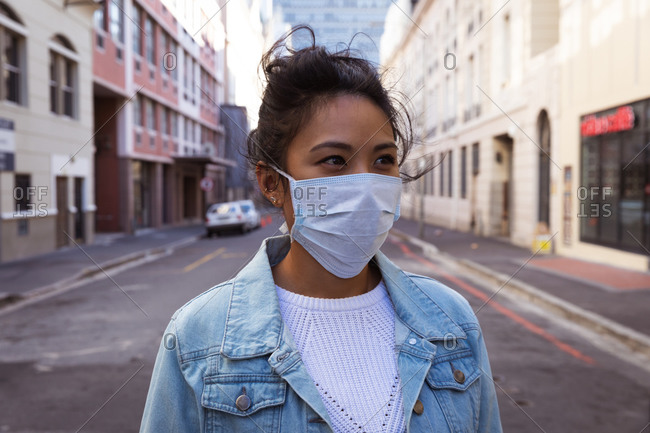 Front view of a mixed race woman with long dark hair out and about in the city streets during the day, wearing a face mask against air pollution and coronavirus, standing in a city street with buildings in the background.