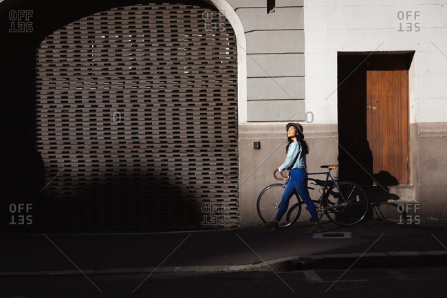 Side view of a happy mixed race woman with long dark hair out and about in the city streets during the day, wearing a hat, jeans and denim jacket, walking with her bicycle with building in the background.