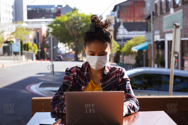 A mixed race woman with dark hair sitting at a table in a cafe working on a laptop computer using a smartphone while wearing a face mask against air pollution and corona virus