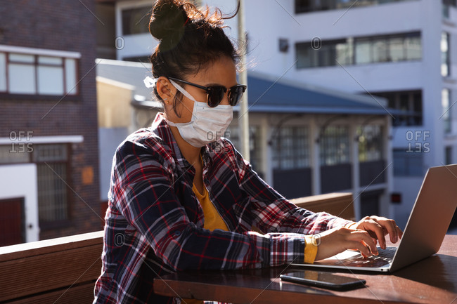 Side view of mixed race woman with dark hair sitting at a table in a cafe working on a laptop computer using a smartphone while wearing sunglasses and face mask against air pollution and corona virus