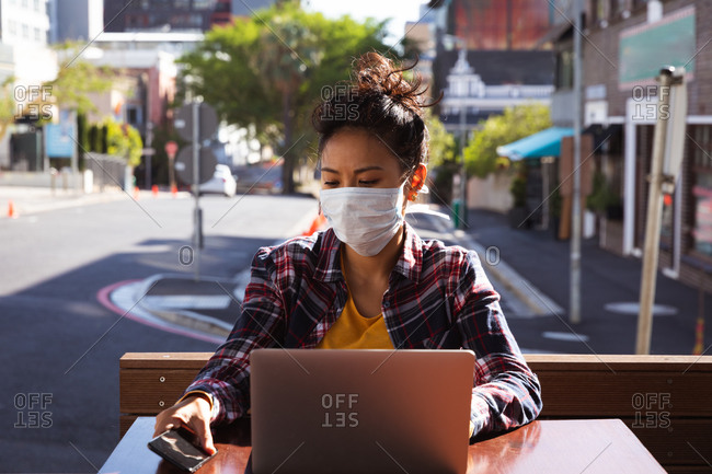 Mixed race woman with dark hair sitting at a table in a cafe working on a laptop computer using a smartphone while wearing a face mask against air pollution and corona virus