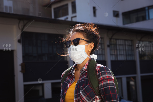 Side view of a mixed race woman with long dark hair out and about in the city streets during the day, wearing sunglasses and a face mask against air pollution and coronavirus, walking in a city street with buildings in the background.