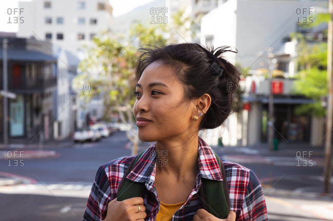 Side view close up of a happy mixed race woman with long dark hair out and about in the city streets during the day, carrying a backpack, wearing a checked shirt smiling with buildings in the background.