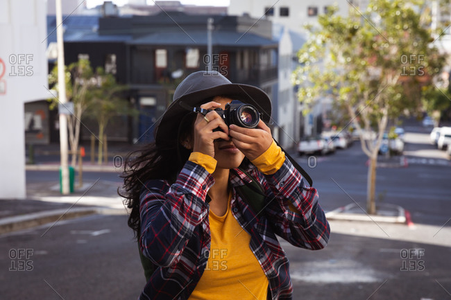 Front view of a mixed race woman with long dark hair out and about in the city streets during the day, using a digital camera, wearing a hat and checked shirt and walking in a city street with buildings in the background.