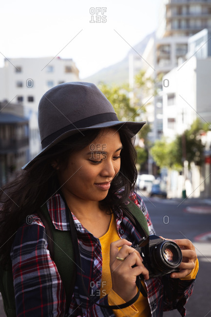Side view close up of a mixed race woman with long dark hair out and about in the city streets during the day, using a digital camera, wearing a hat and checked shirt and walking in a city street with buildings in the background.