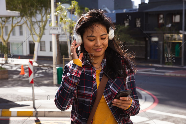 Front view of a mixed race woman with long dark hair out and about in the city streets during the day, using a smartphone, wearing headphones, a checked shirt and walking in a city street with buildings in the background.