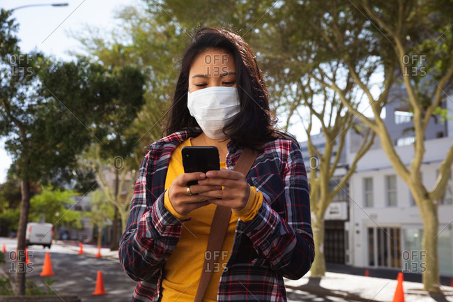 Mixed race woman with long dark hair wearing a face mask against air pollution and corona virus while standing and using a smartphone with trees and city buildings behind her