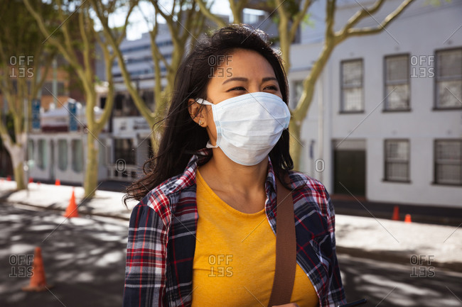 Side view of a mixed race woman with long dark hair out and about in the city streets during the day, wearing a face mask against air pollution and coronavirus, standing in a city street with buildings in the background.