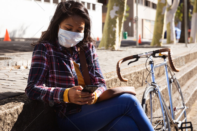 Side view of a mixed race woman with dark hair out and about in the city streets during the day, wearing sunglasses and a face mask against air pollution and coronavirus, sitting on steps using a smartphone, her bike next to her with buildings in the background.