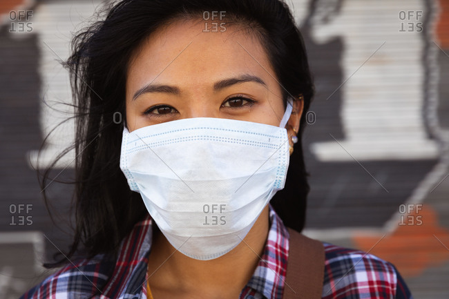 Portrait of a mixed race woman with long dark hair out and about in the city streets during the day, wearing a face mask against air pollution and coronavirus, standing looking at camera with wall in the background.