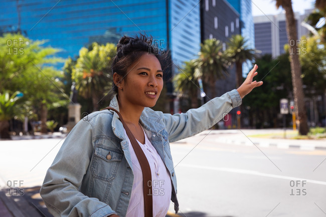 Side view of a happy mixed race woman with long dark hair out and about in the city streets during the day, standing in a city street raising her arm to stop a taxi, wearing a denim jacket smiling with buildings in the background.
