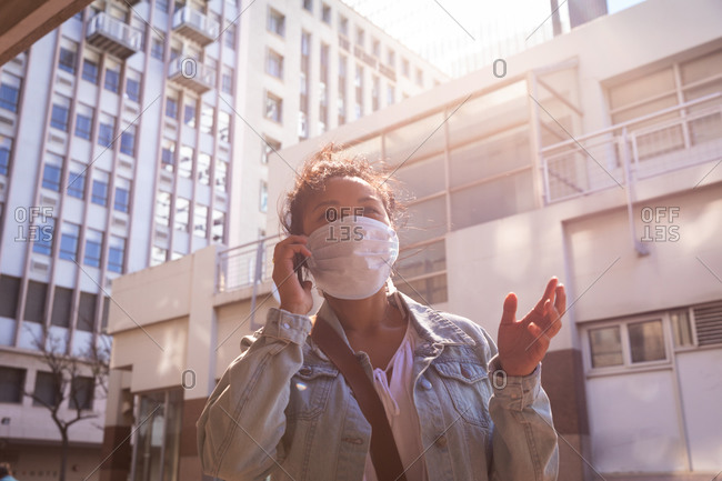 Low angle front view of a mixed race woman with long dark hair out and about in the city streets during the day, wearing a face mask against air pollution and coronavirus, standing and talking on the smartphone with buildings in the background.