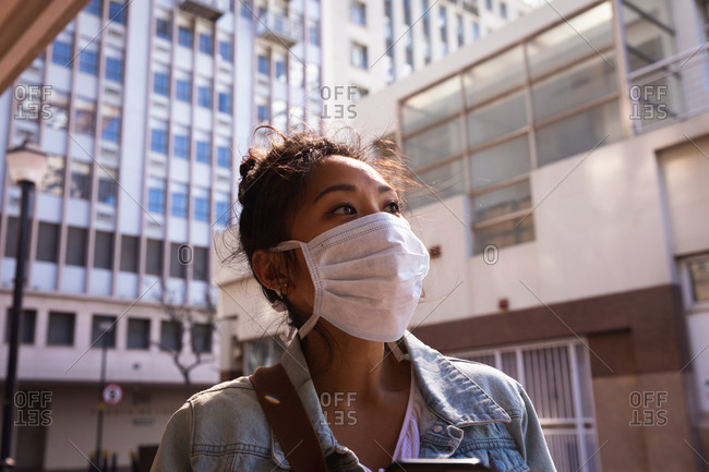Low angle side view of a mixed race woman with long dark hair out and about in the city streets during the day, wearing a face mask against air pollution and coronavirus, standing with buildings in the background.