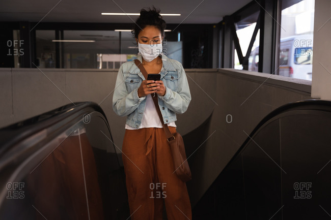 Front view of a mixed race woman with long dark hair out and about in the city streets during the day, wearing a face mask against air pollution and coronavirus, standing on escalator and using a smartphone with metro train station in the background.