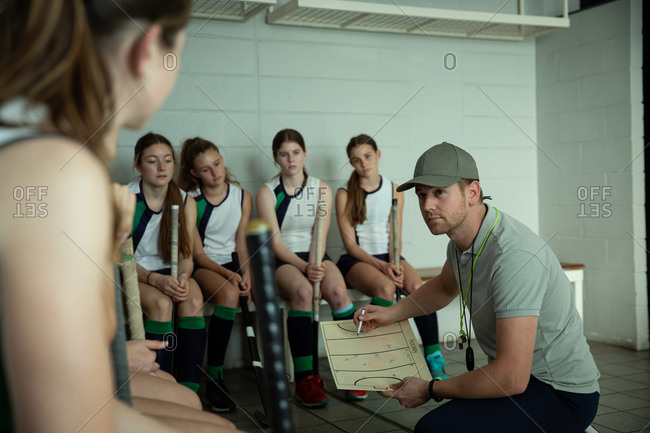 Side view of a Caucasian male field hockey coach interacting with a multi-ethnic group of female field hockey players, sitting in a changing room, showing them a game plan