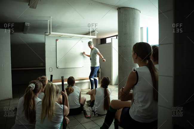 Side view of a Caucasian male field hockey coach interacting with a group of female Caucasian field hockey players, sitting in a changing room, showing them a game plan, writing on a whiteboard