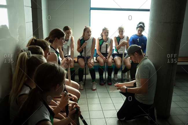 Side view of a Caucasian male field hockey coach interacting with a group of female Caucasian field hockey players, sitting in a changing room, showing them a game plan
