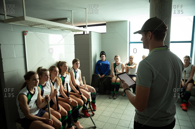 Side view of a Caucasian male field hockey coach interacting with a group of female Caucasian field hockey players, sitting in a changing room, holding a digital tablet
