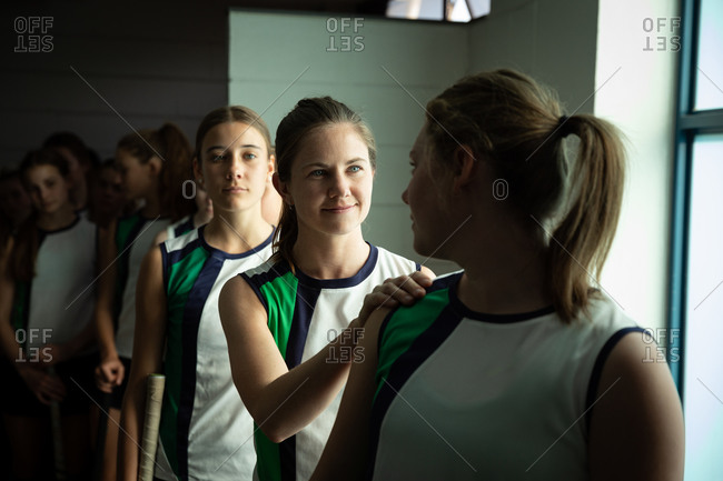 Front view of a group of female Caucasian field hockey players preparing before a game, standing in a changing room, one is putting her hand on a shoulder of her teammate