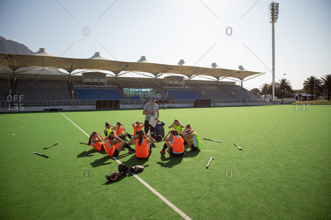 Side view of a group of female Caucasian field hockey players and their Caucasian field hockey coach, training before a game, working out on a field hockey pitch, exercising, doing sit ups, on a sunny day