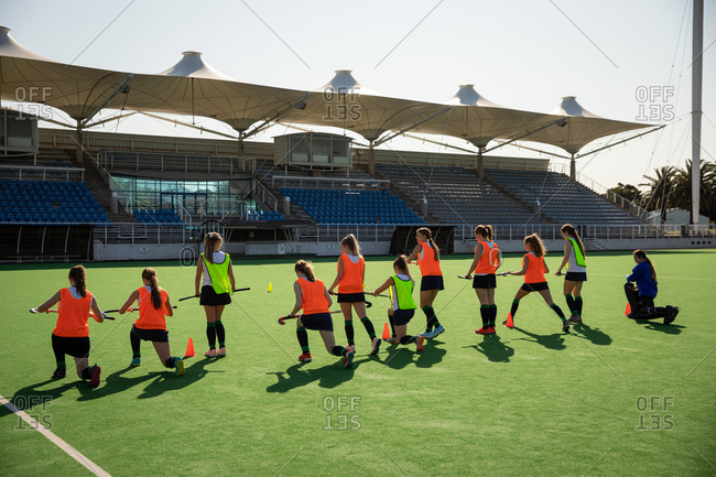 Side view of a group of female Caucasian field hockey players and their Caucasian male field hockey coach, training before a game, working out on a field hockey pitch, doing exercises, stretching their legs, holding hockey sticks on a sunny day