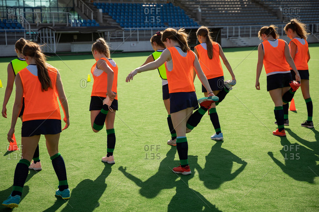 Side view of a group of female Caucasian field hockey players and their Caucasian male field hockey coach, training before a game, working out on a field hockey pitch, doing exercises, stretching their legs, holding their feet behind their back on a sunny day