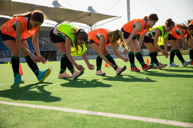 Side view of a group of female Caucasian field hockey players, training before a game, working out on a field hockey pitch, doing exercises, stretching their legs, bending down to their feet on a sunny day