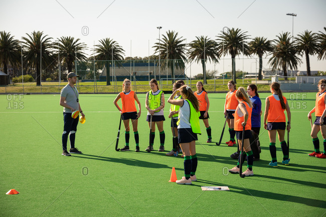 Side view of a group of female Caucasian field hockey players and their Caucasian male field hockey coach, training before a game, working out on a field hockey pitch, doing exercises, preparing for shooting training on a sunny day