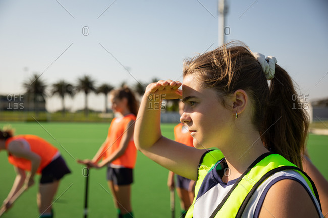 Side view of a Caucasian female field hockey player training before a game, working out on a hockey pitch, shading her eyes from the sun, with her teammates in the background, on a sunny day