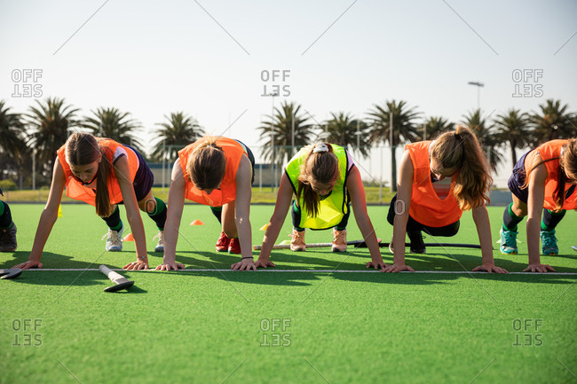 Front view of a group of female Caucasian field hockey players, training before a game, working out on a field hockey pitch, doing push ups, on a sunny day
