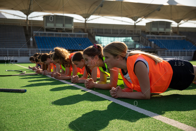 Side view of a group of female Caucasian field hockey players, training before a game, working out on a field hockey pitch, doing planks, on a sunny day