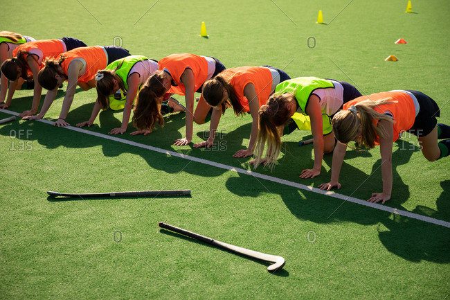 Side view of a group of female Caucasian field hockey players, training before a game, working out on a field hockey pitch, doing strength exercises , on a sunny day
