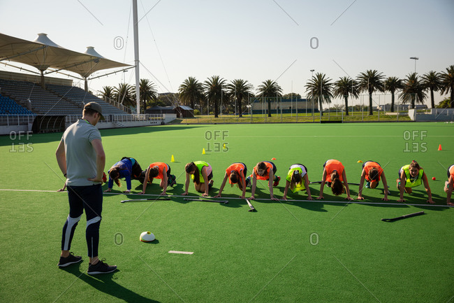 Front view of a group of female Caucasian field hockey players and their Caucasian male field hockey coach, training before a game, working out on a field hockey pitch, doing strength exercises, on a sunny day