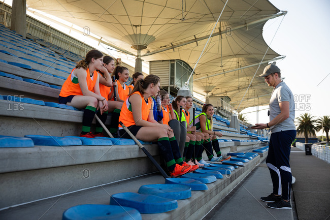 Side view of a group of female Caucasian field hockey players preparing before a game, sitting on a stand, holding hockey sticks, with their Caucasian male field hockey coach standing in front of them, talking about game plan on a sunny day
