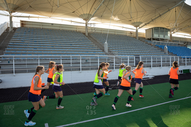 Side view of a group of female Caucasian field hockey players and their Caucasian male field hockey coach, training before a game, working out on a field hockey pitch, doing exercises, running, on a sunny day