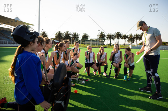 Side view of a group of female Caucasian field hockey players preparing before a game, kneeling in front of their Caucasian male coach, on a hockey pitch, who gives them game plan, on a sunny day