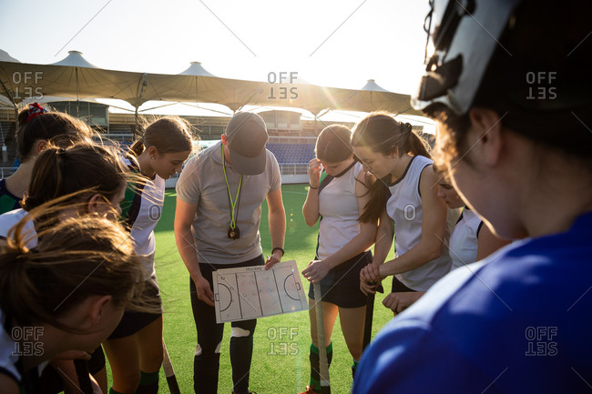 Side view of a group of female Caucasian field hockey players preparing before a game, huddling around their Caucasian male coach, on a hockey pitch, who gives them game plan, on a sunny day