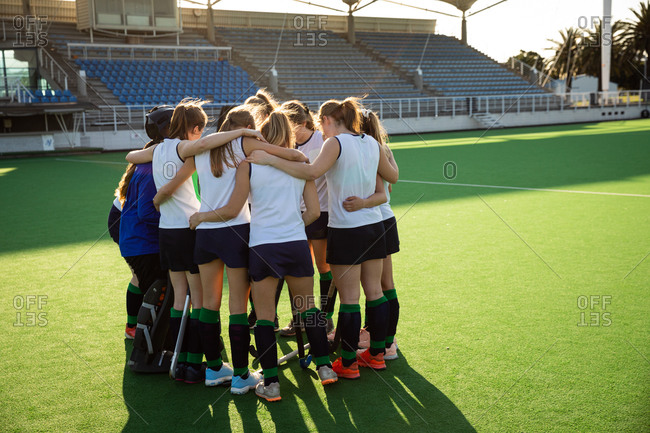 Side view of a group of female Caucasian field hockey players, preparing before a game, concentrating, motivating, huddling, on a sunny day