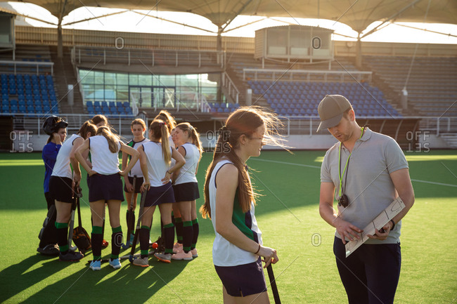 Side view of a group of female Caucasian field hockey players, preparing before a game, huddling, with one player talking to her Caucasian male coach in the foreground, on a sunny day