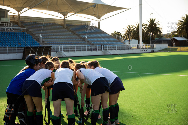 Side view of a group of female Caucasian field hockey players, preparing before a game, huddling, interacting, motivating, bending down, on a sunny day