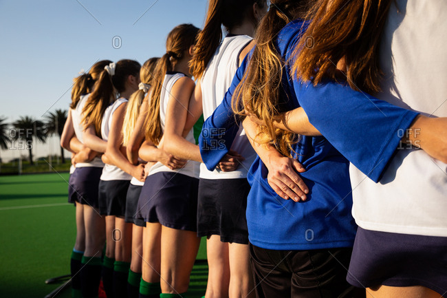 Rear view of a group of female Caucasian field hockey players, preparing before a game, standing in a row embracing, on a sunny day