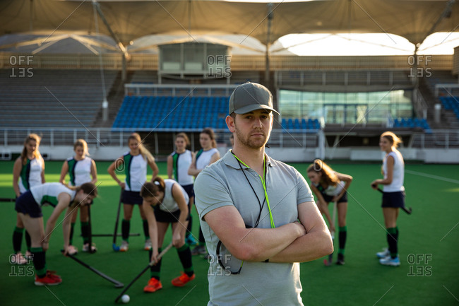 Portrait of a Caucasian male field hockey coach, preparing his team for a game, standing on a hockey pitch, looking at camera, with his team playing with a ball in the background on a sunny day