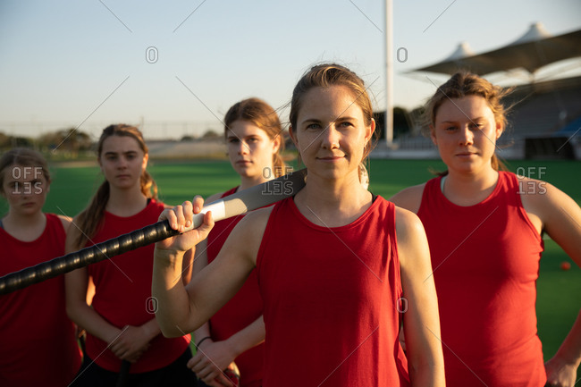 Portrait of a Caucasian female field hockey player standing on a hockey pitch with a hockey stick on her shoulder looking at camera with her teammates standing in a row behind her on a sunny day